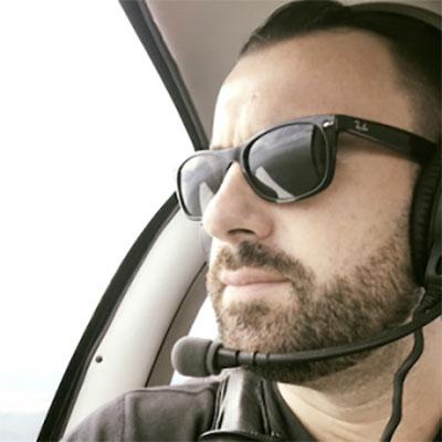 Image of Ryan Scibelli, who is wearing sunglasses and sitting in a helicopter